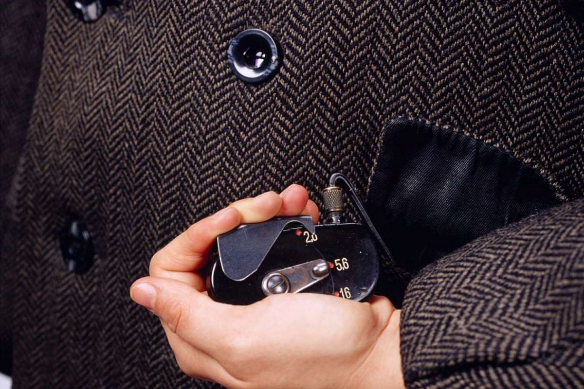 A handout photo of a hidden coat camera issued by the KGB around 1970. The lens was embedded in the double-breasted jacket's right middle button. To snap a picture, the spy would squeeze a shutter cable hidden in the coat pocket.