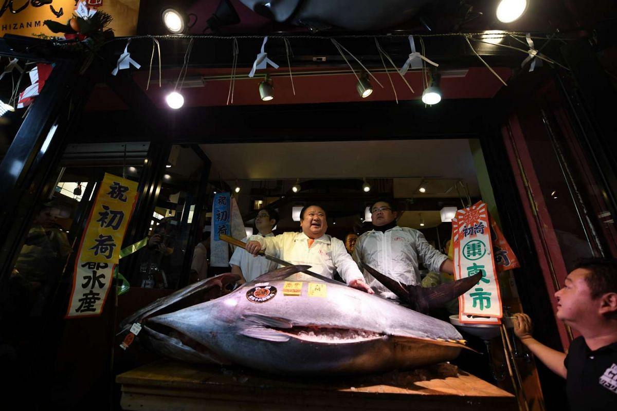Kiyoshi Kimura (centre), posing with a 212 kg bluefin tuna at his main restaurant near the Tsukiji fish market in Tokyo, on Jan 5, 2017.