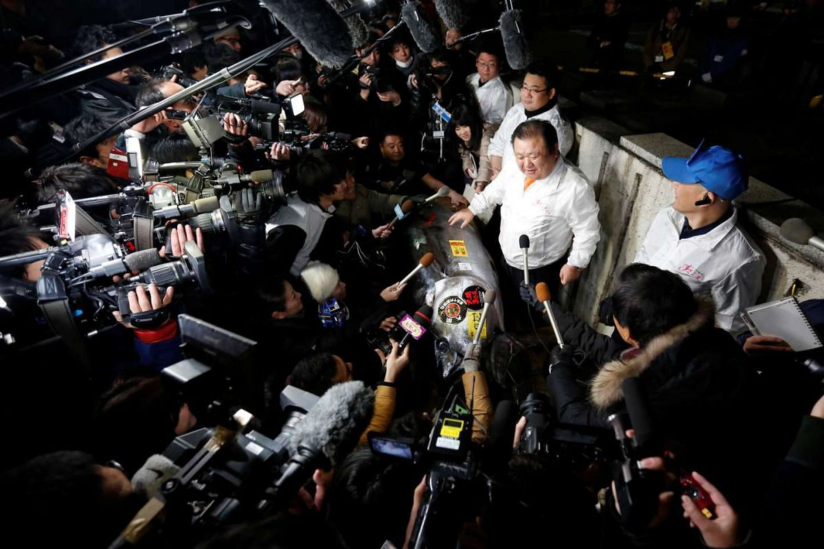 Kiyoshi Kimura (centre), who runs a chain of sushi restaurants, Sushi Zanmai, is surrounded by media as he speaks next to a 212 kg bluefin tuna at Tsukiji fish market in Tokyo, on Jan 5, 2017.