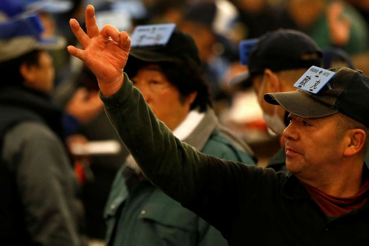A wholesaler showing a hand sign to an auctioneer during the New Year's auction of the frozen tuna at the Tsukiji fish market in Tokyo, on Jan 5, 2017.