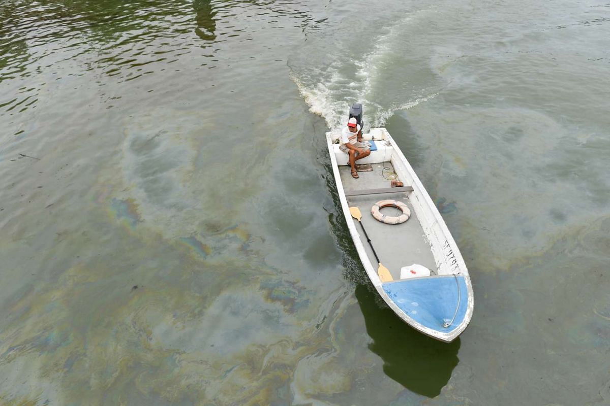 A man sits on a boat surrounded by oil stained waters at Changi Beach.