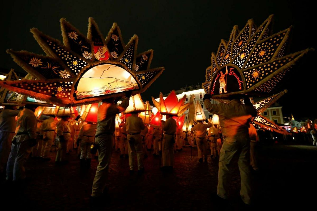 """Participants of """"Gloecklerlauf"""" (bell ringers run) wear """"Lichterkappen"""" (light caps) made of paper and wood while ringing bells on their belts during a traditional parade in Gmunden, Austria, on Jan 5, 2017."""