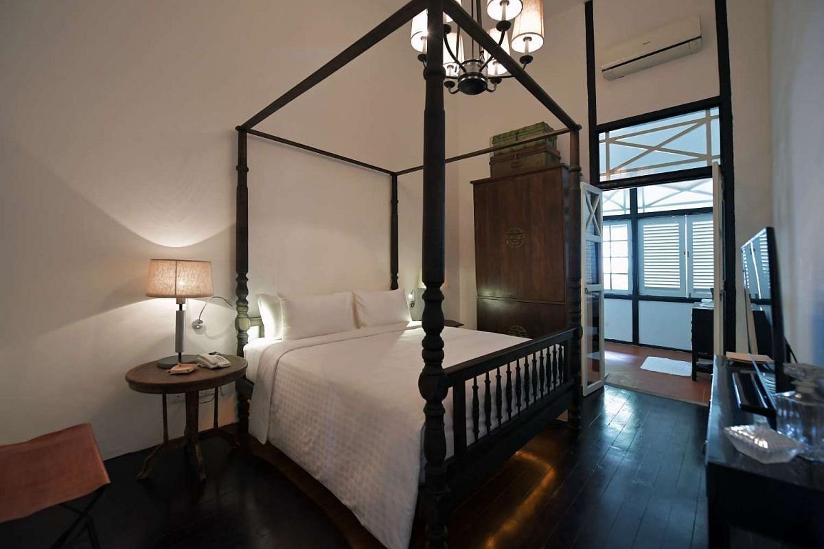 Lush greenery and water features add to the hotel's soothing ambience; and a four-poster bed (above) in one of the rooms complements the colonial feel of the property.