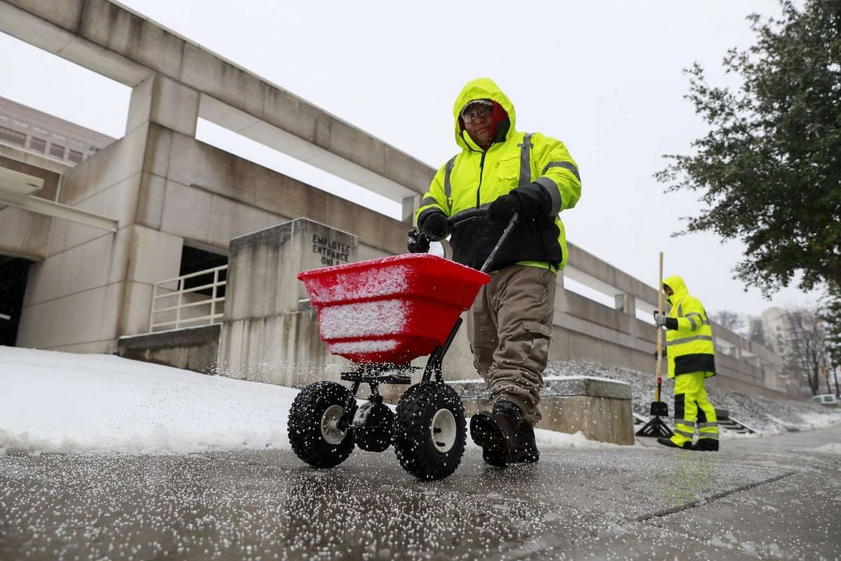 A worker applying salt to a sidewalk after a winter storm moved through Charlotte, North Carolina.