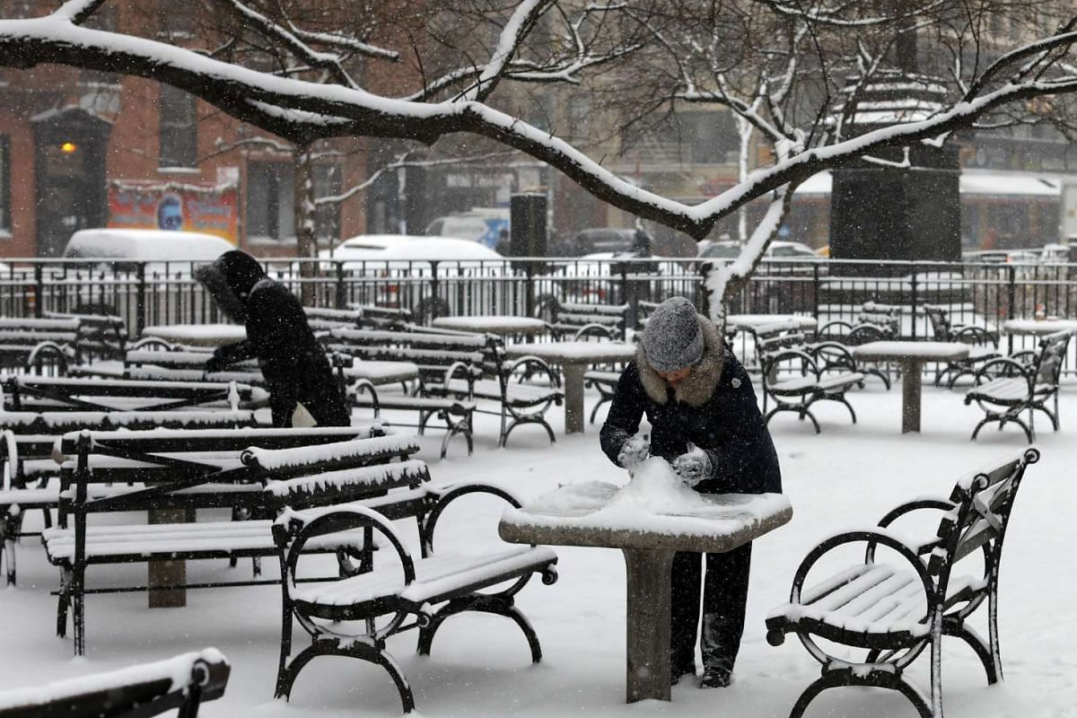 A couple of women attempting to build a snowman in Tompkins Square Park in New York.