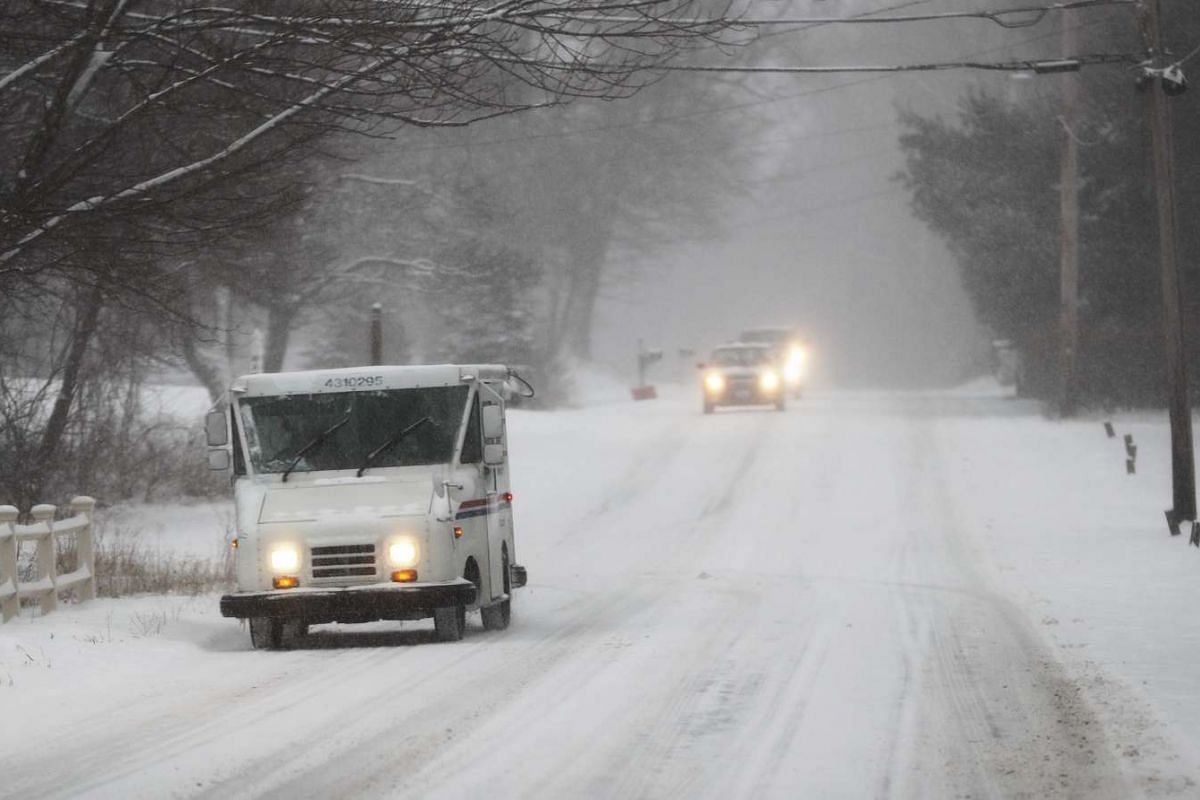 A United States Postal Service truck making deliveries along a snow-covered road.