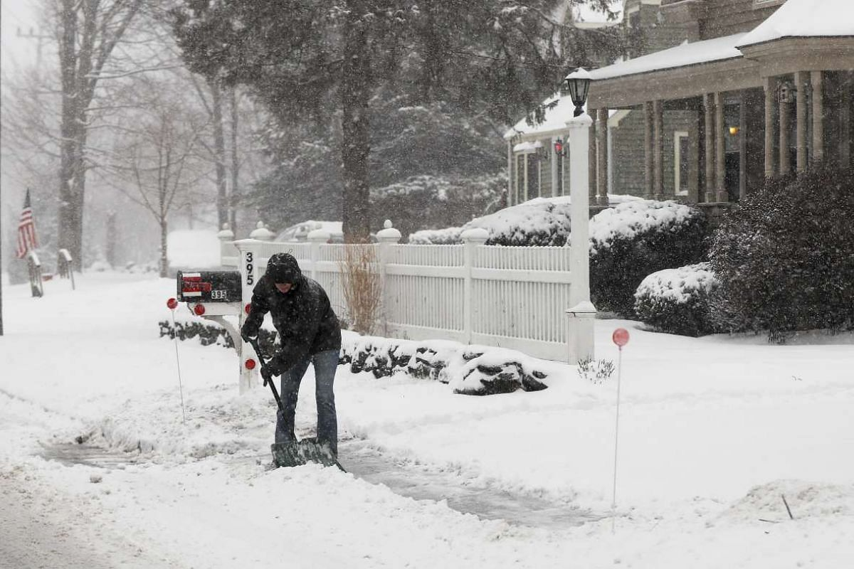 A woman shovelling a driveway as snow begins to fall from a storm system which has delivered winter weather across the US.