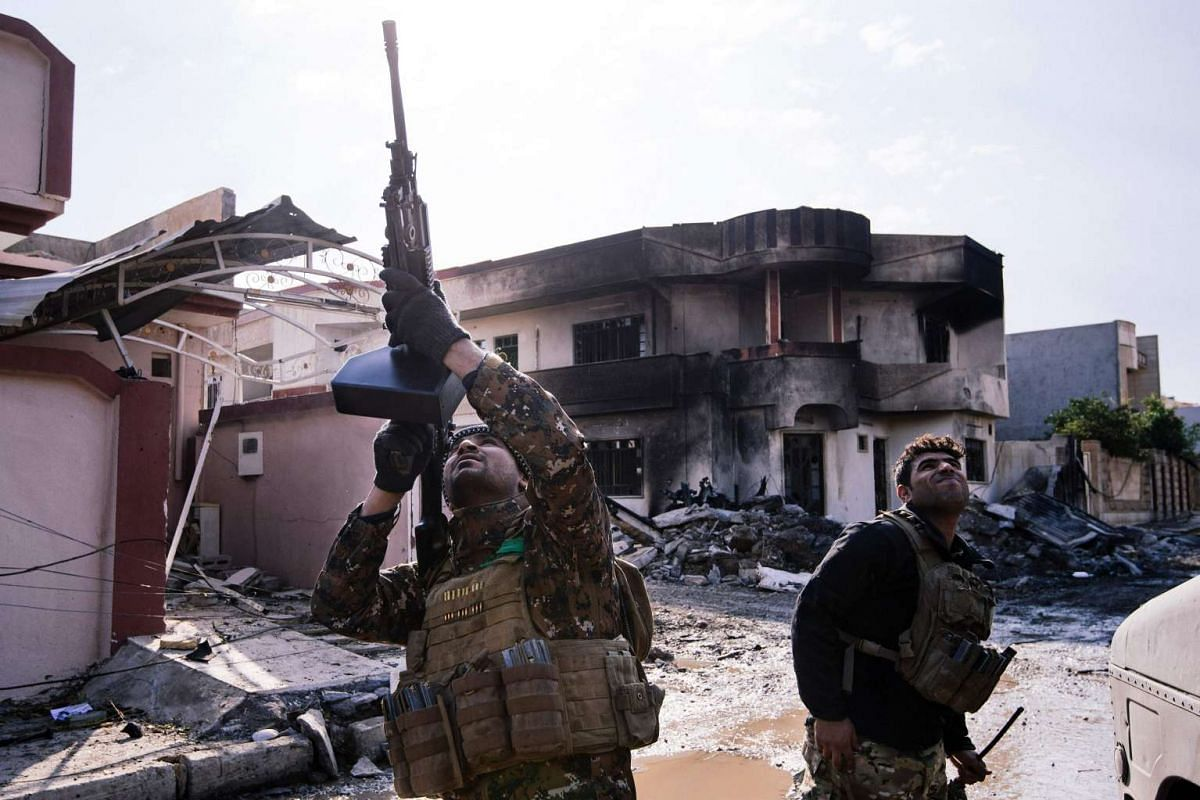 An Iraqi special forces Counter Terrorism Service (CTS) member shoots at a drone flown by Islamic State group jihadists (IS) in Mosul's al-Rifaq neighbourhood on January 8, 2017, as an ongoing military operation against the militants continues. PHOTO