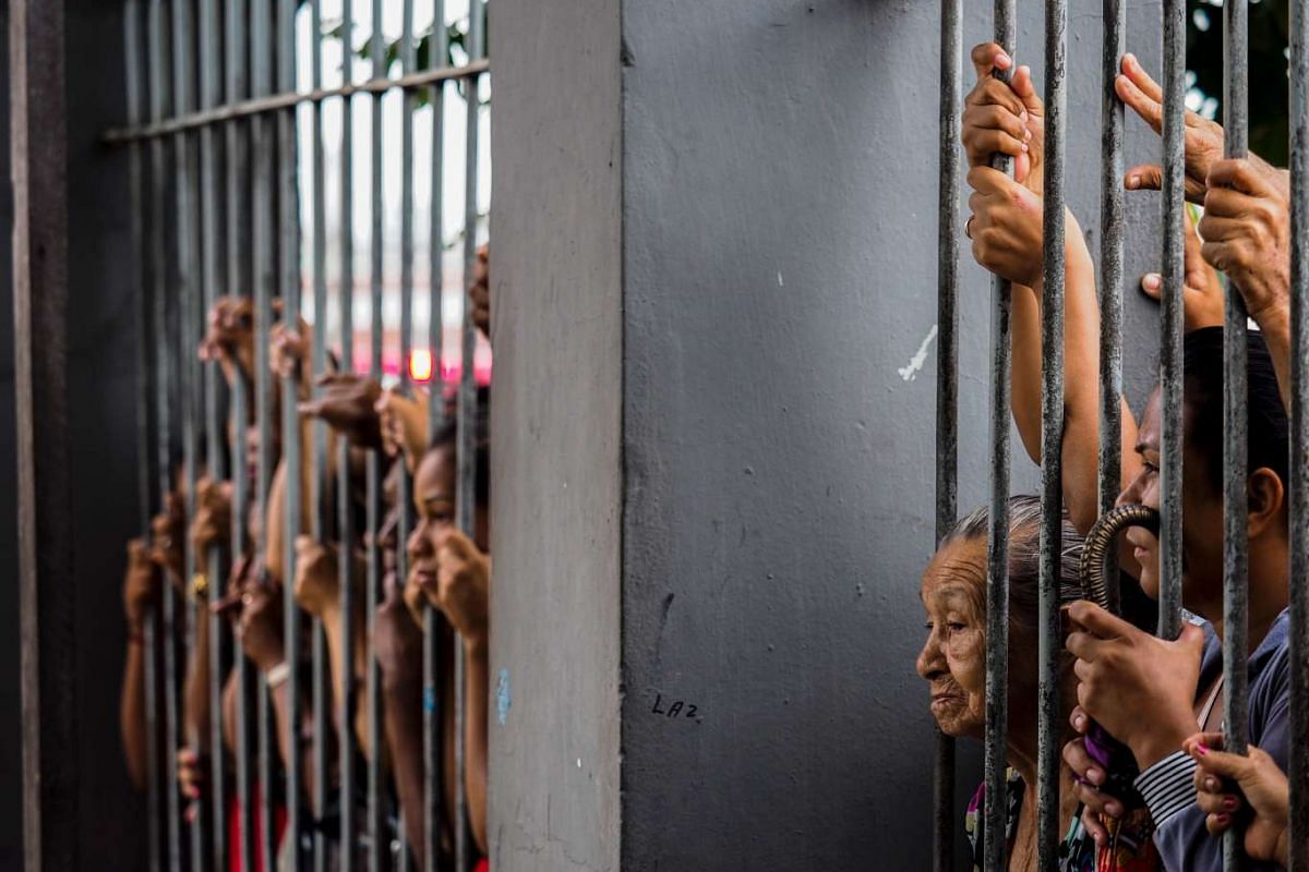 Relatives wait for information following a riot that ended with at least four prisoners killed inside Desembargador Raimundo Vidal Pessoa Public Jail, on January 8, 2017, in Manaus, Amazonas, Brazil. PHOTO: AFP