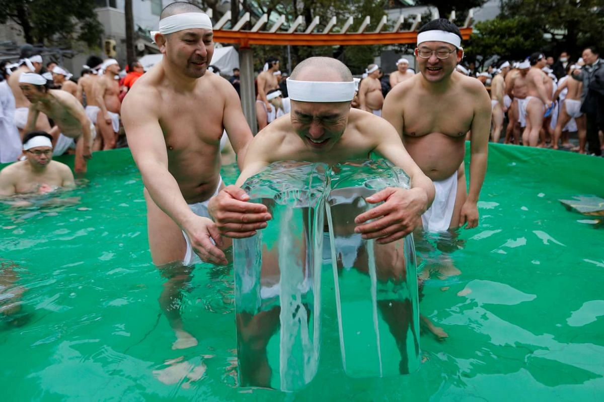 Men wearing loin cloths hold on to ice as they bathe in ice-cold water outside the Teppozu Inari shrine in Tokyo, Japan, January 8, 2017. According to organizers, about 100 participants took part in the Shinto ceremony to purify their souls and wish