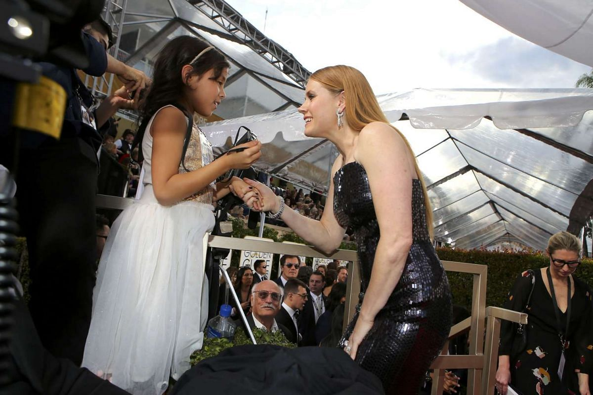 Actress Amy Adams greets a fan as she arrives at the 74th Annual Golden Globe Awards in Beverly Hills, California, U.S., January 8, 2017. PHOTO: REUTERS