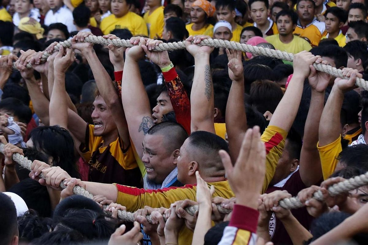 Filipino devotees holding on to a cord that pulls a carriage with the statue of the Black Nazarene during a procession in Manila, Philippines, on Jan 9, 2017.