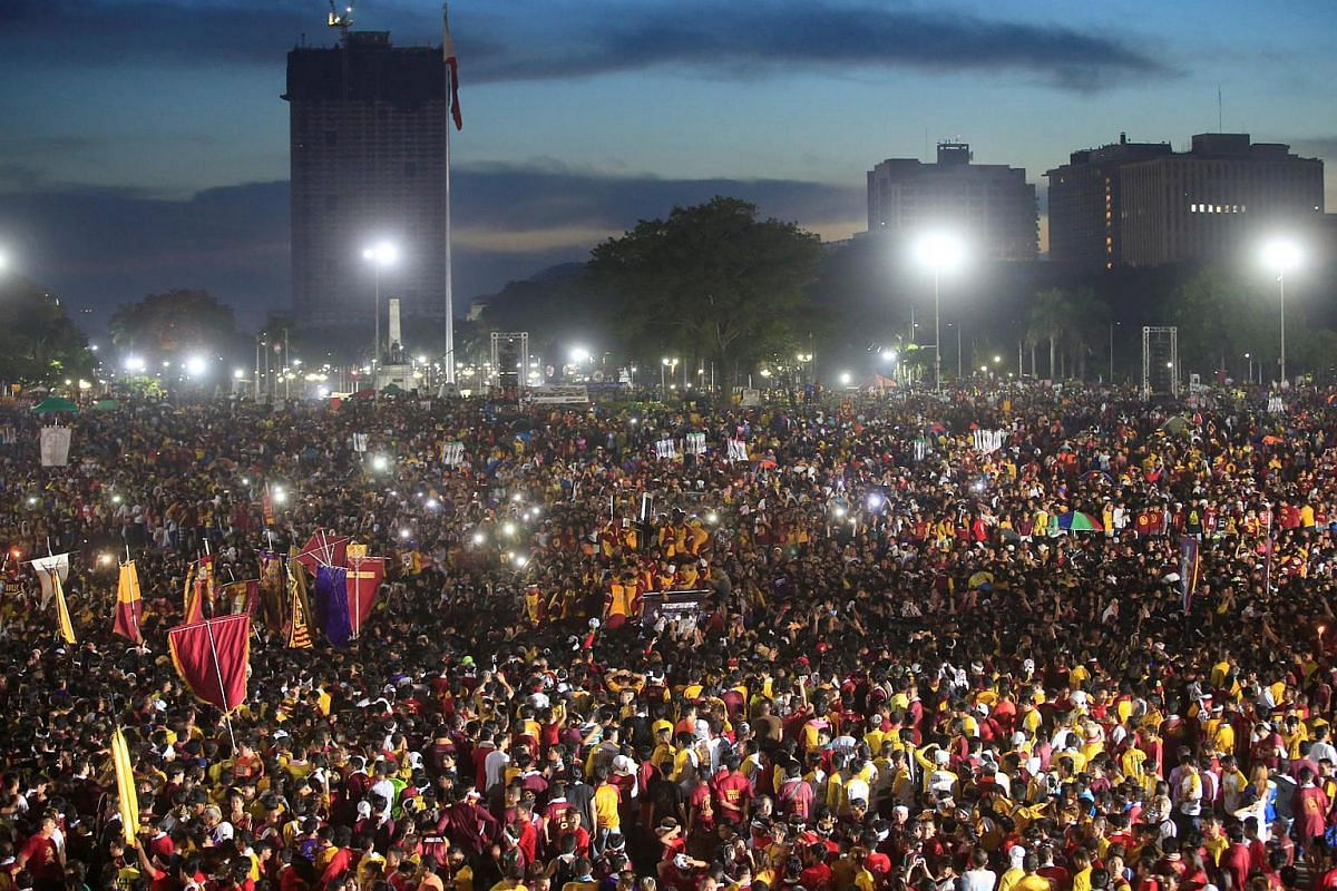 The carriage carrying the Black Nazarene (centre) is surrounded by devotees during an annual procession in Rizal park, metro Manila, Philippines, on Jan 9, 2017.