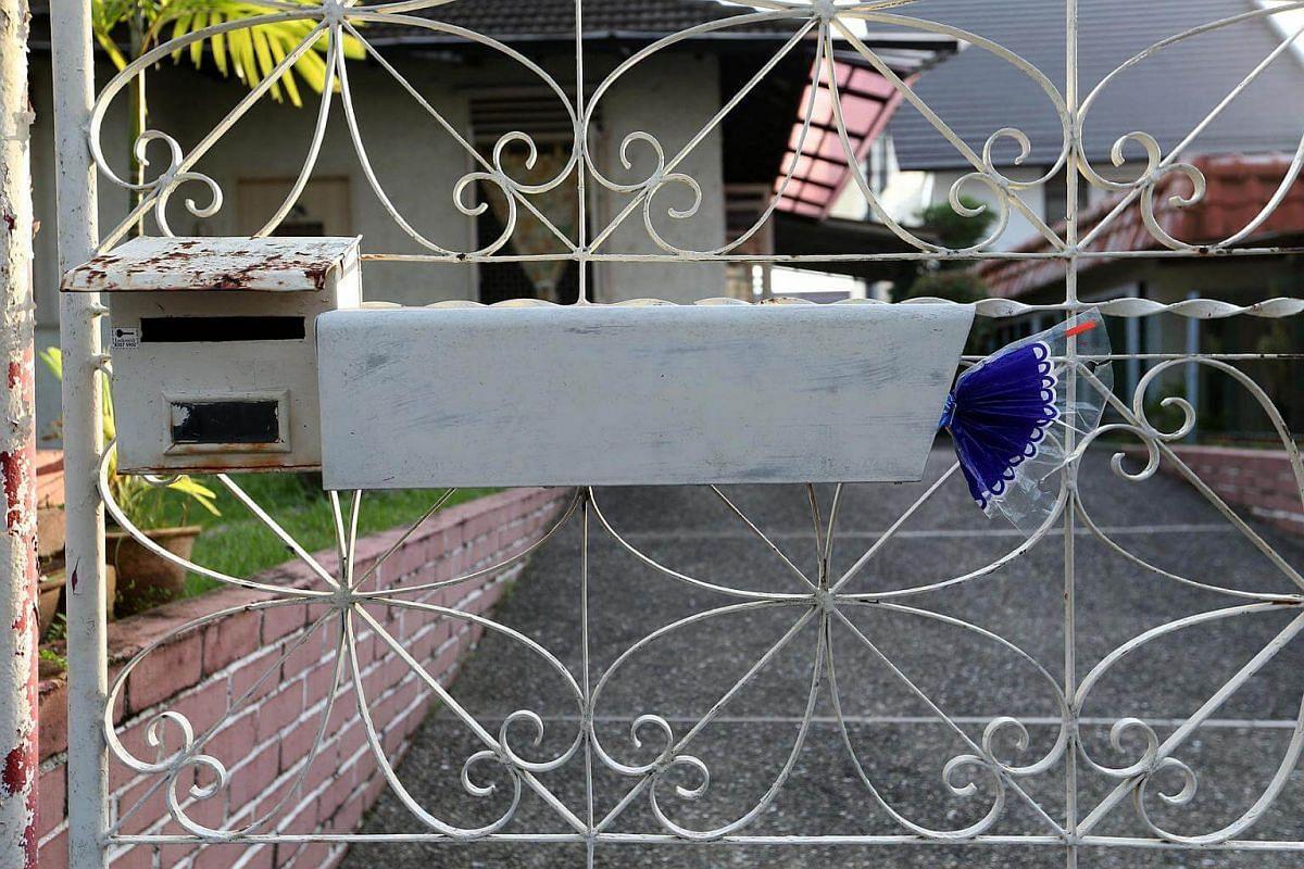 Mr Foo placing a loaf of Gardenia bread in a mailbox in Serangoon Gardens.