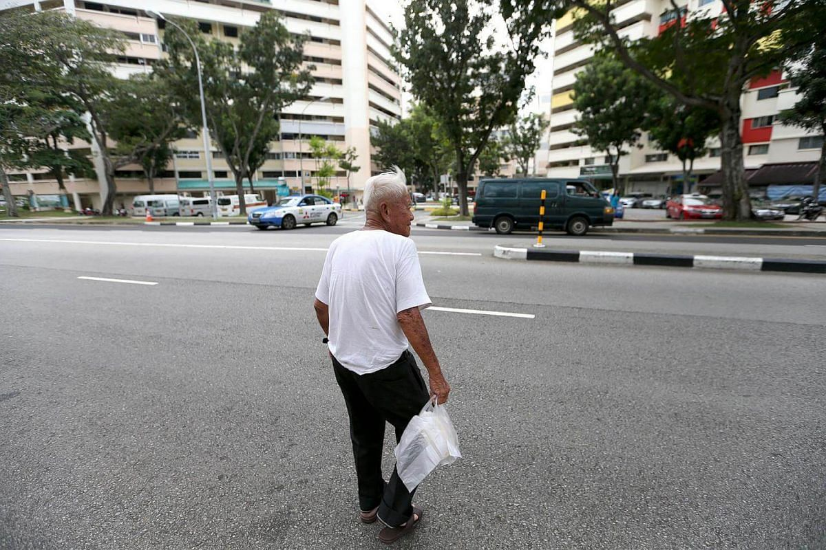 Mr Foo crossing the road and heading towards his van, after picking up a loaf of traditional white bread without crust from a bakery in Serangoon Central.