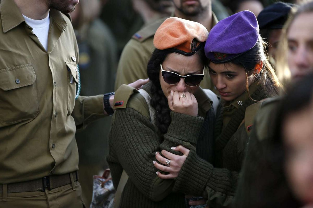 Israeli soldiers mourn at the grave of Israeli Army lieutenant Yael Yekutiel after his funeral at the Kiryat Shaul Military Cemetery in Tel Aviv, Israel, January 9, 2017. Yekutiel was one of the four Israeli soldiers killed in a truck attack in Jerus
