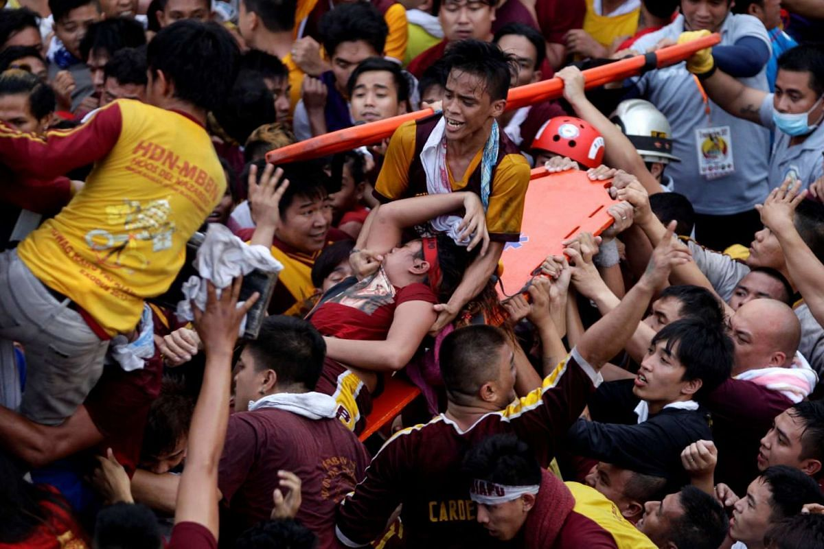 Devotees carry a woman who fainted while taking part in the annual procession of the Black Nazarene in Manila, Philippines January 9, 2017. PHOTO: REUTERS