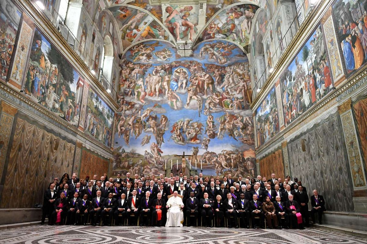 Pope Francis poses in the Sistine Chapel with members of the diplomatic corps accredited to the Holy See at the end of an audience for the traditional exchange of New Year greetings at the Vatican January 9, 2017. REUTERS/POOL