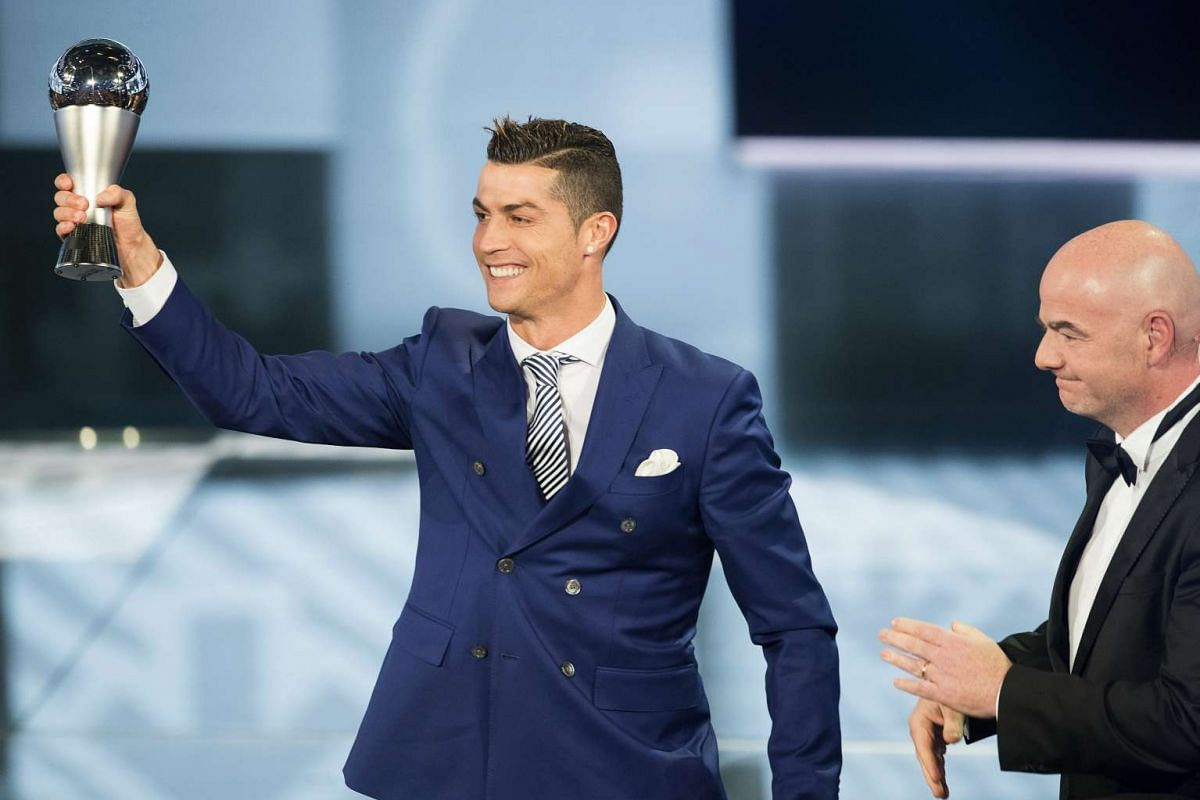 Real Madrid's Portuguese striker Cristiano Ronaldo (L) lifts his trophy after winning the FIFA Men's Player of the Year 2016 award next to FIFA President Gianni Infantino (R) during the FIFA Awards 2016 gala at the Swiss TV studio in Zurich, Switzerl