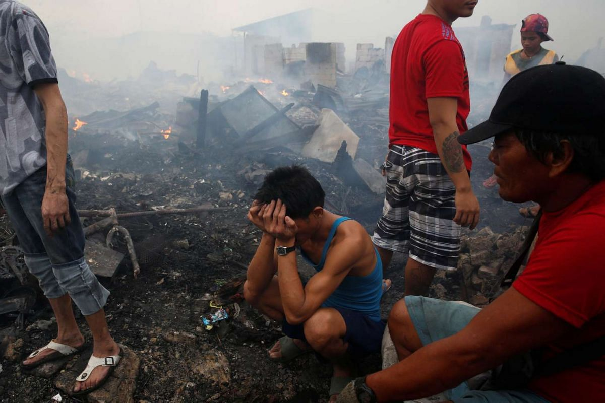 A man tries to come to terms with what remains of his home after a fire razed a squatter colony in Navotas, Metro Manila, in the Philippines on Jan 10, 2017.