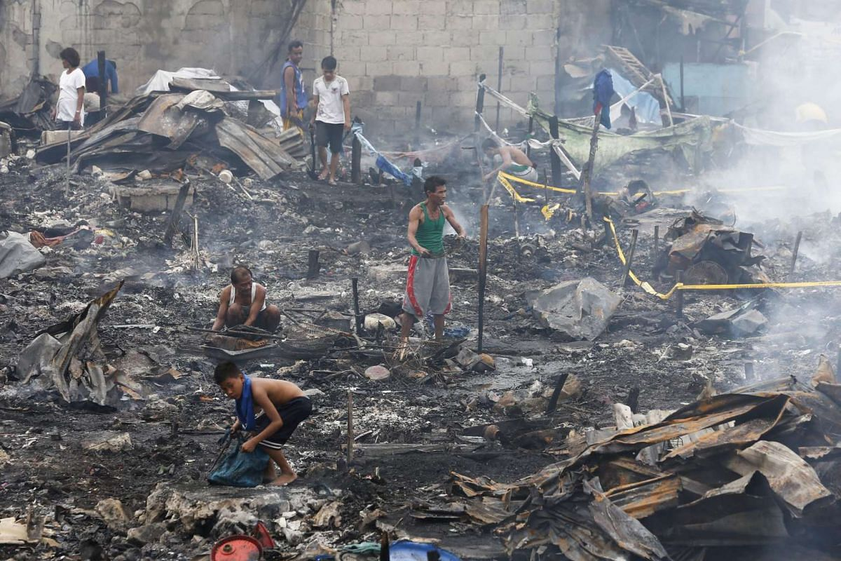 Filipino residents in the aftermath of the fire that destroyed their homes in Navotas.