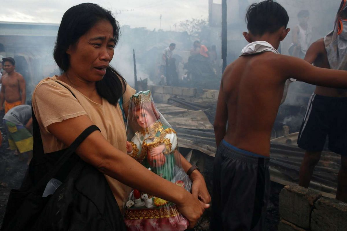 A woman carries an image of Baby Jesus that she was able to save, after her family's house was destroyed in a fire at a squatter colony in Navotas, Metro Manila, in the Philippines.