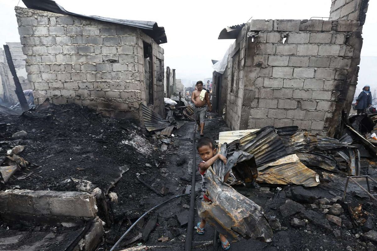 A Filipino child does his part to carry off scrap metal from burned homes after the fire in Navotas, Metro Manila, in the Philippines. Initial reports stated that some 600 homes were destroyed.
