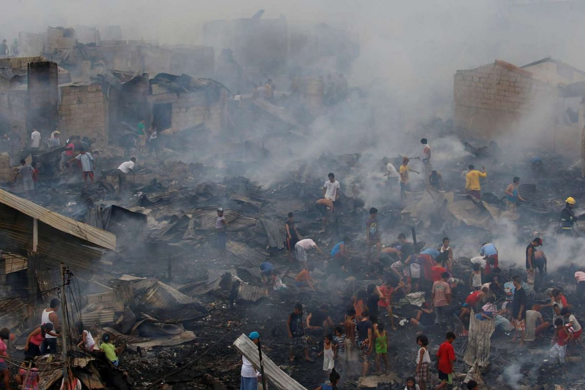 Residents sift through the ruins of their homes after a fire at a squatter colony in Navotas, Metro Manila, in the Philippines.