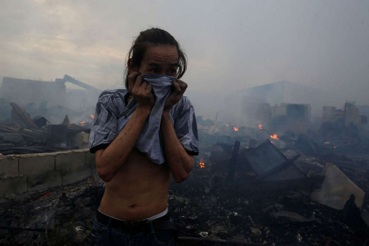 A victim covers his nose amid smoke next to the ruins of houses on Jan 10, 2017, after a fire at a squatter colony in Navotas, Metro Manila, in the Philippines.