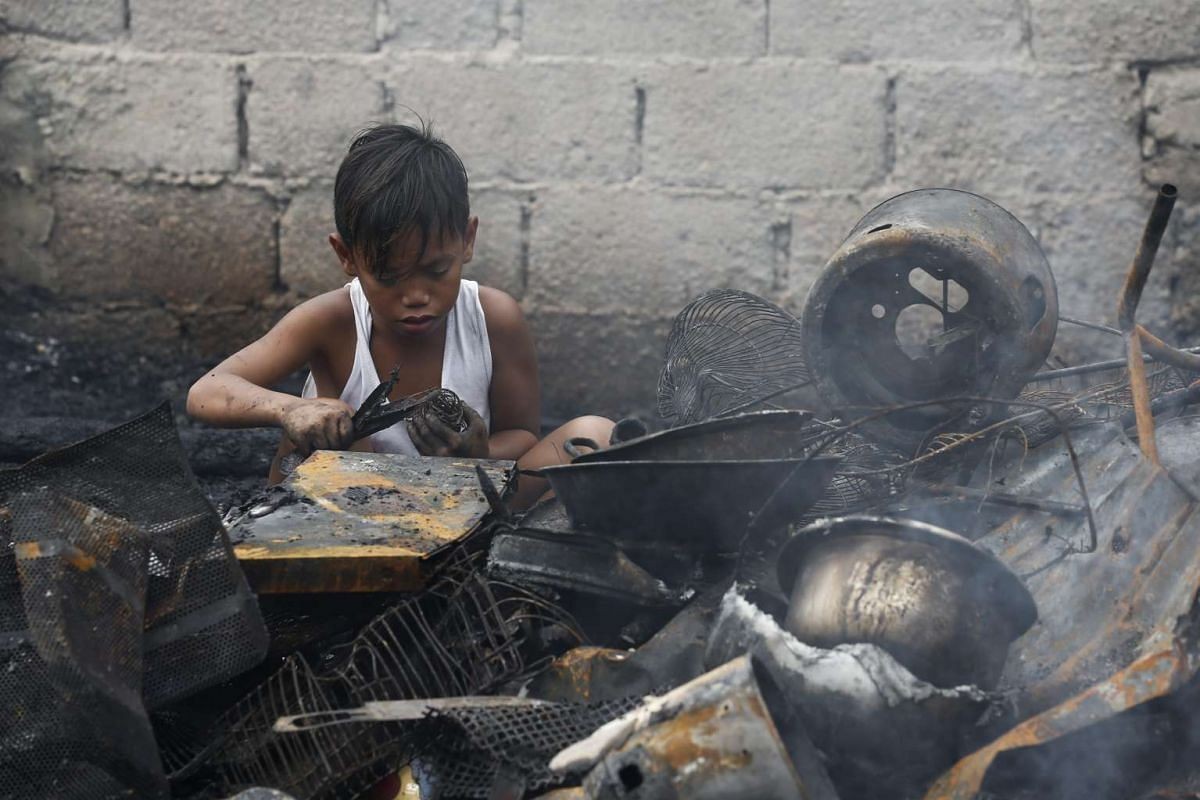 A child looks for scrap metal amidst debris from burned homes after the fire in Navotas, Metro Manila, in the Philippines.