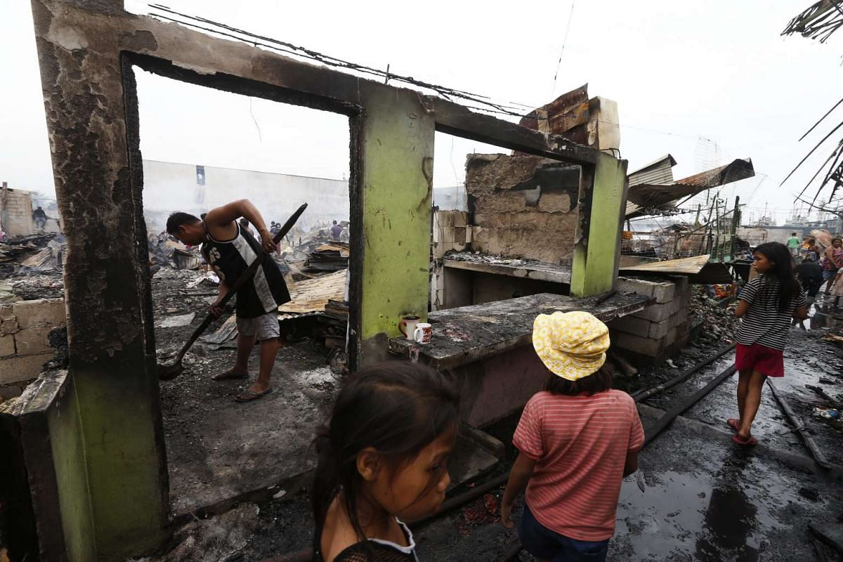 Residents return to their burned homes to look for any recoverable belongings after the fire in Navotas, Metro Manila, in the Philippines.