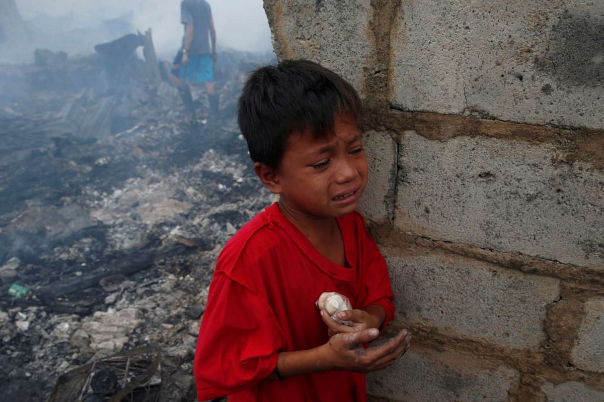 A Filipino boy in tears after injuring his hand while recovering scrap metal.