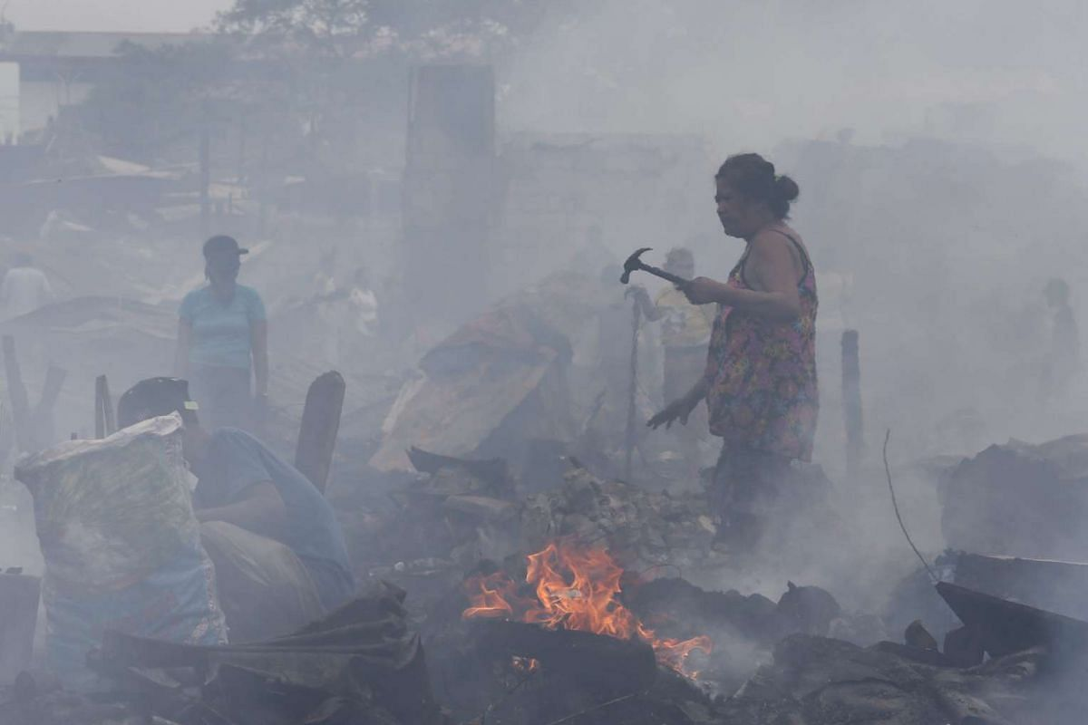 A woman looks for whatever she can salvage from the ruins of her home.