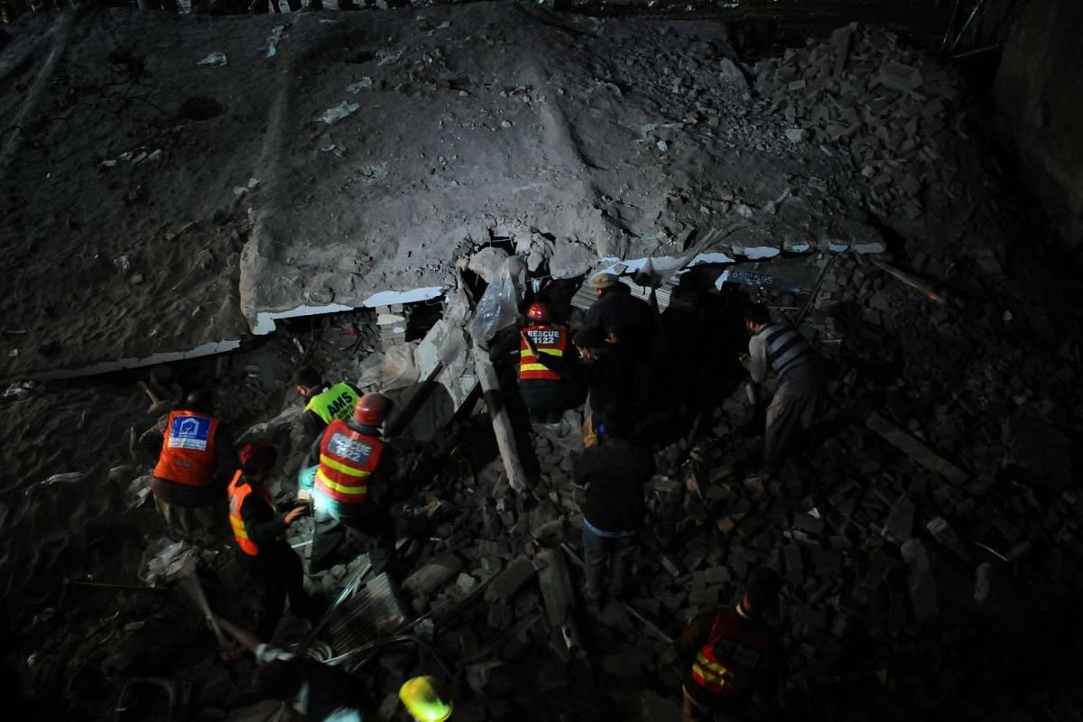 Rescue workers search for bodies in the debris in a collapsed building in Multan, Pakistan, January 10, 2017. PHOTO: EPA
