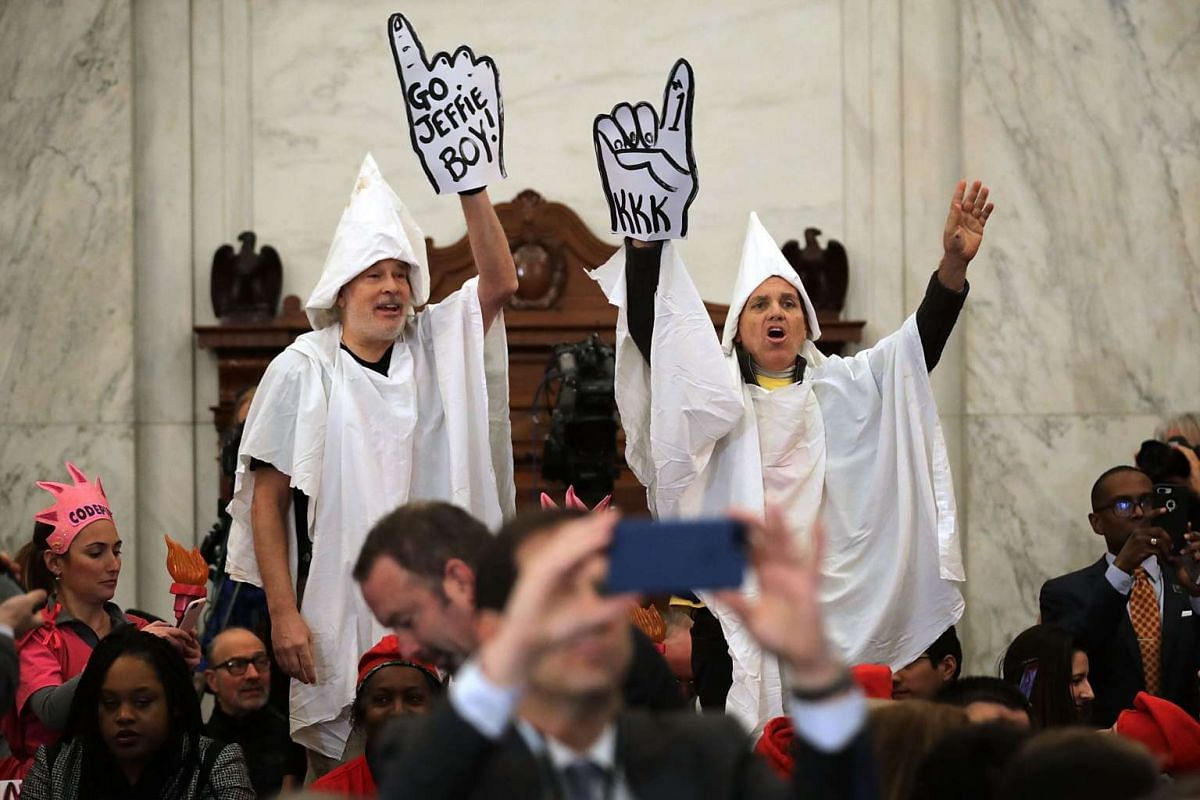 Protesters wearing white sheets shout at Sen. Jeff Sessions (R-AL) as he arrives for his confirmation hearing to be the U.S. attorney general Senate Judiciary Committee in the Russell Senate Office Building on Capitol Hill January 10, 2017 in Washing