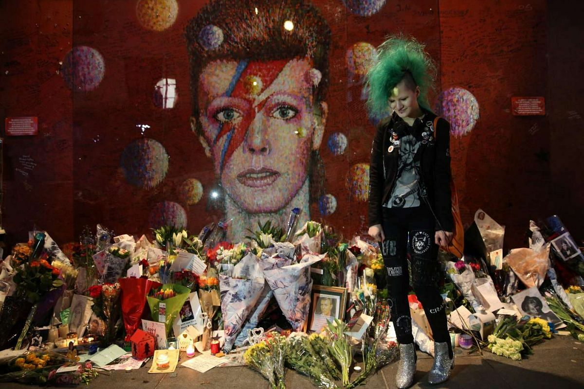 A David Bowie fan poses in front of the mural of late British pop icon David Bowie created by Australian street artist James Cochran, also known as Jimmy C, as fans payed their respects in Brixton, south London on January 10, 2017, on the first anniv