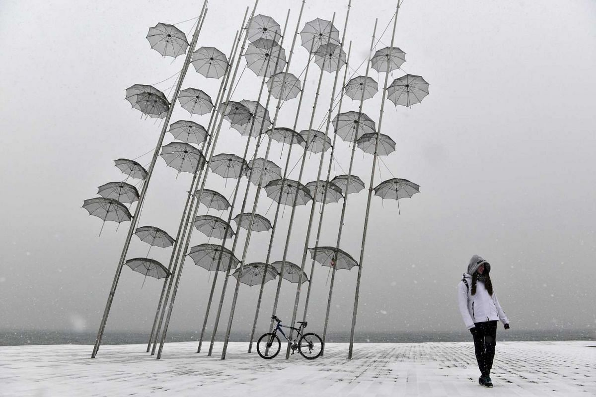 A woman poses next to Greek sculptor artist George Zongolopoulos' 'Umbrellas,' during heavy snowfall in Thessaloniki on January 10, 2017. PHOTO: AFP