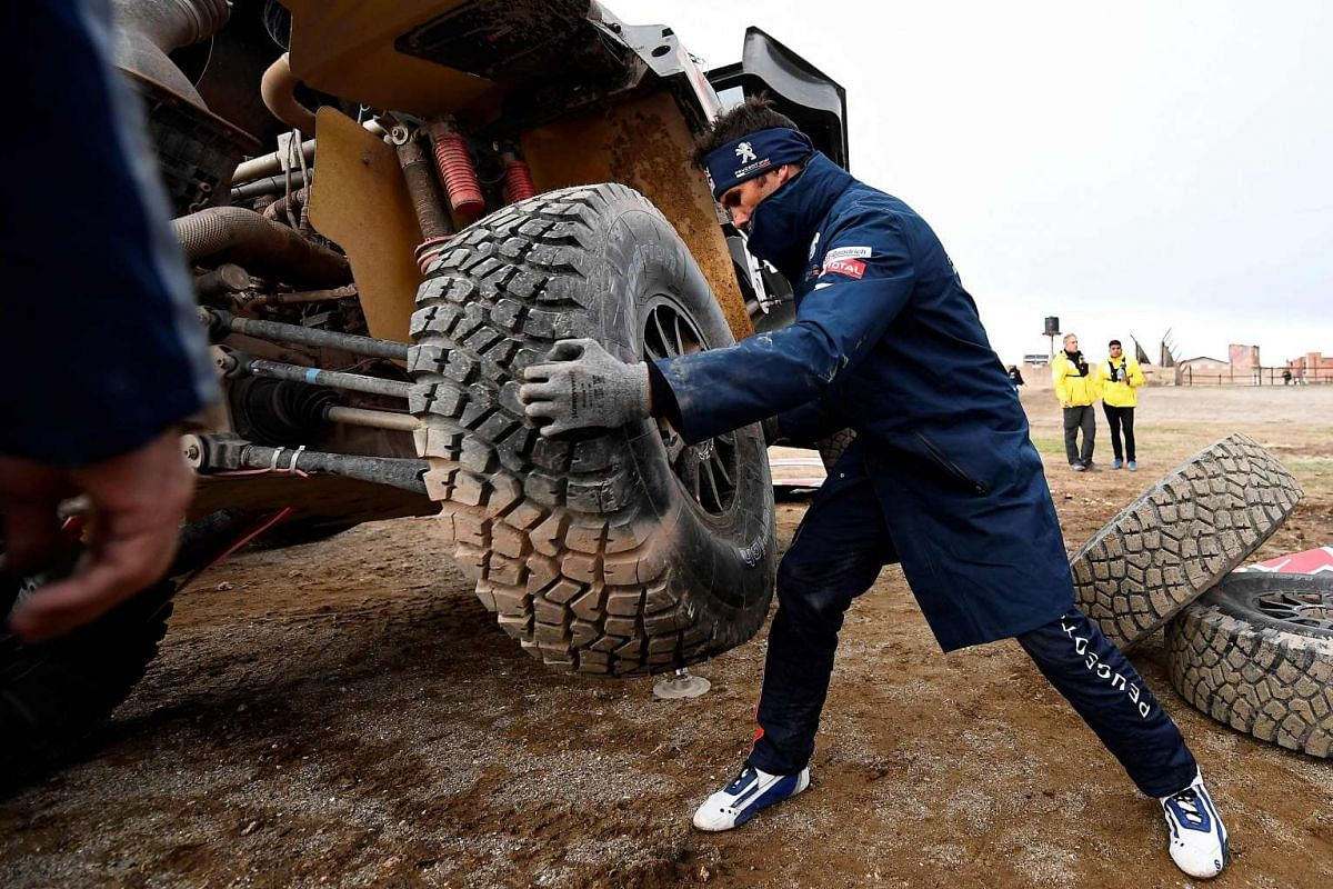 Peugeot's French pilot Cyril Despres working on his car at the bivouac in Uyuni, Bolivia, after Stage 7 of the Dakar Rally between La Paz and Uyuni, on Jan 9, 2017.