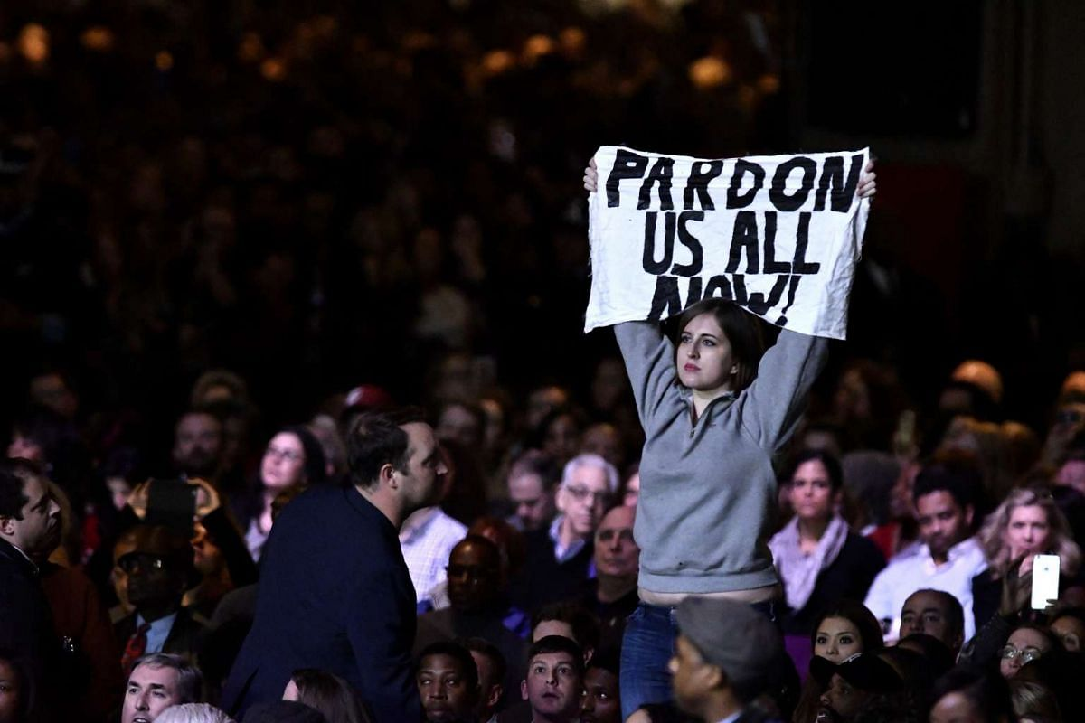 "A protester holds up a sign reading ""Pardon Us All Now"" during a farewell speech by US President Barack Obama in Chicago, Illinois on Jan 10, 2017."