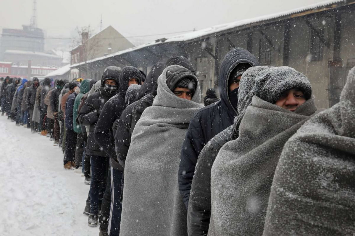 Migrants wait in line to receive a plate of free food during a snowfall outside a derelict customs warehouse in Belgrade, Serbia, January 11, 2017. PHOTO: REUTERS