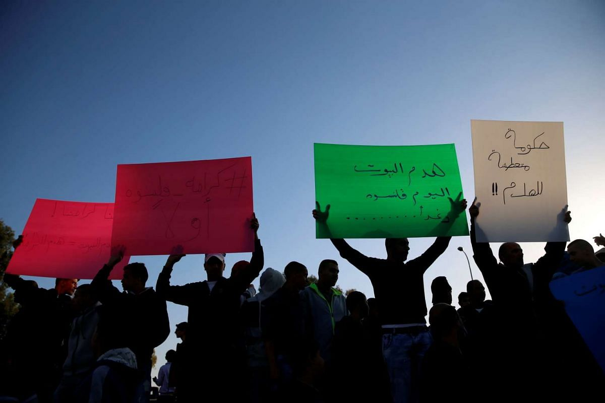 Israeli Arabs hold posters to protest against the demolishing of their houses by Israeli bulldozers in the northern Israeli city of Qalansuwa, January 11, 2017. PHOTO: REUTERS