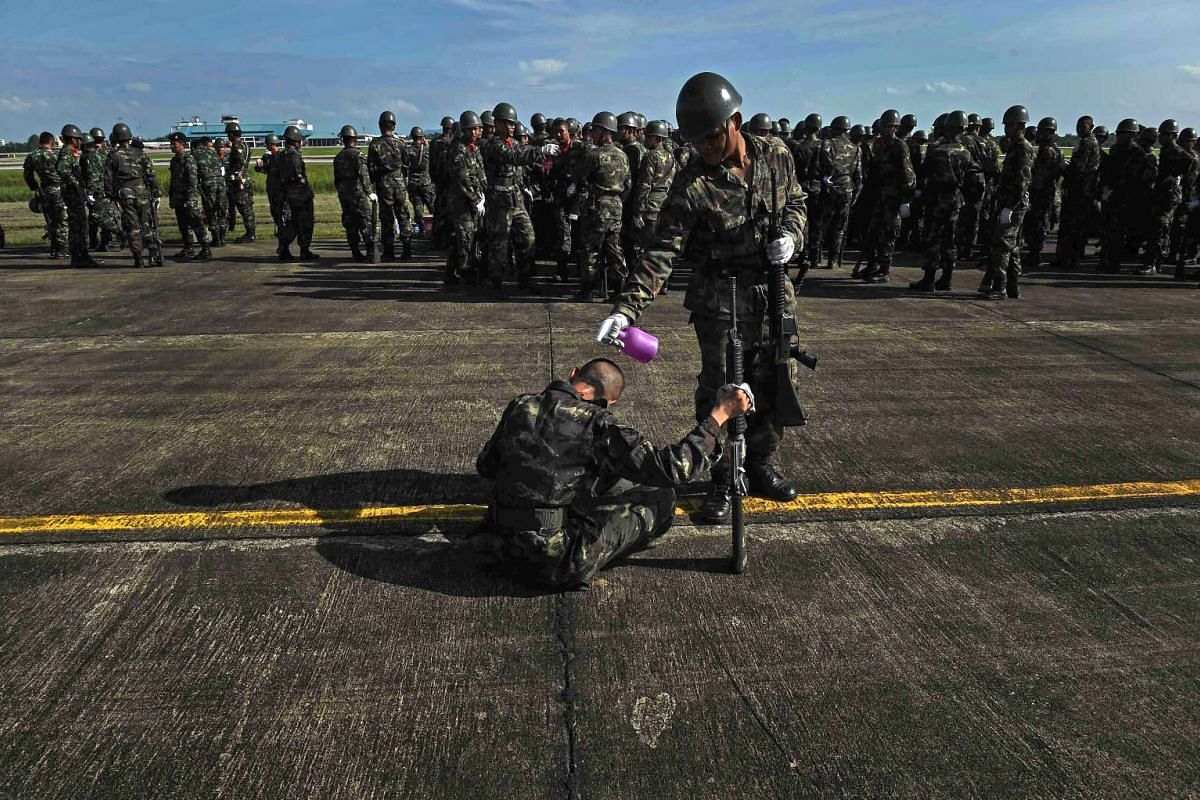 A Royal Thai Air Force soldier sprays another soldier with a bottle to cool him off during drill practice at Surat Thani Airport in Thailand's southern province of Surat Thani on January 11, 2017. PHOTO: AFP