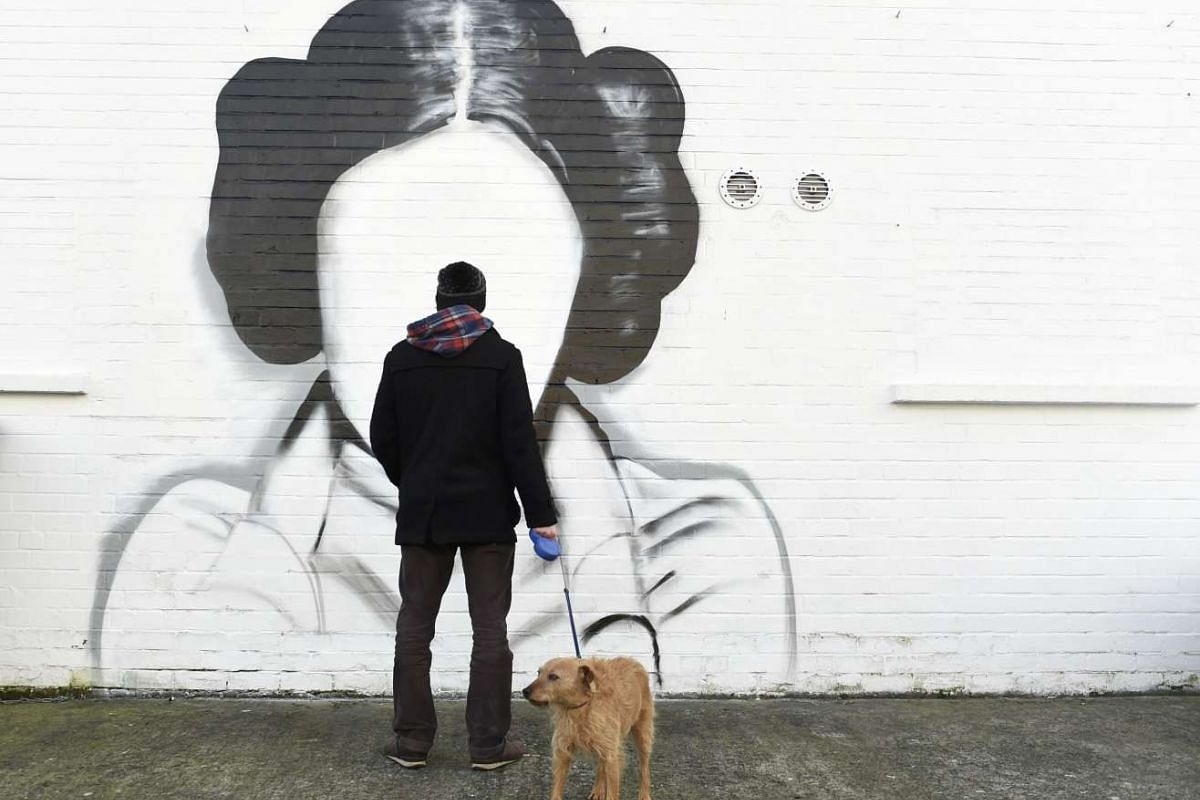 A man and his dog stop to look at a mural depicting Princess Leia from the film Star Wars played by Carrie Fisher in Belfast, Northern Ireland January 11, 2017. PHOTO: REUTERS