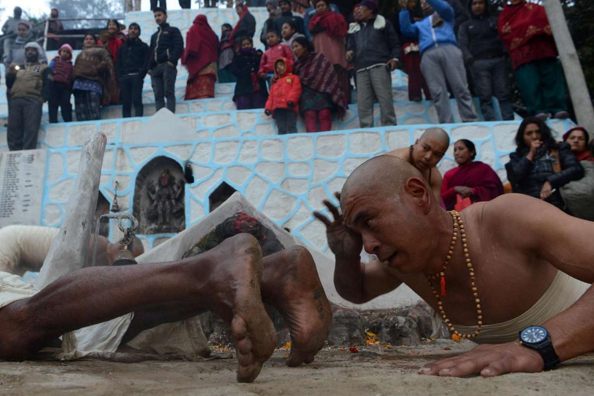 Nepalese Hindu devotees roll on the ground after bathing in the Shali River on the outskirts of Kathmandu, Nepal on Jan 12, 2017.