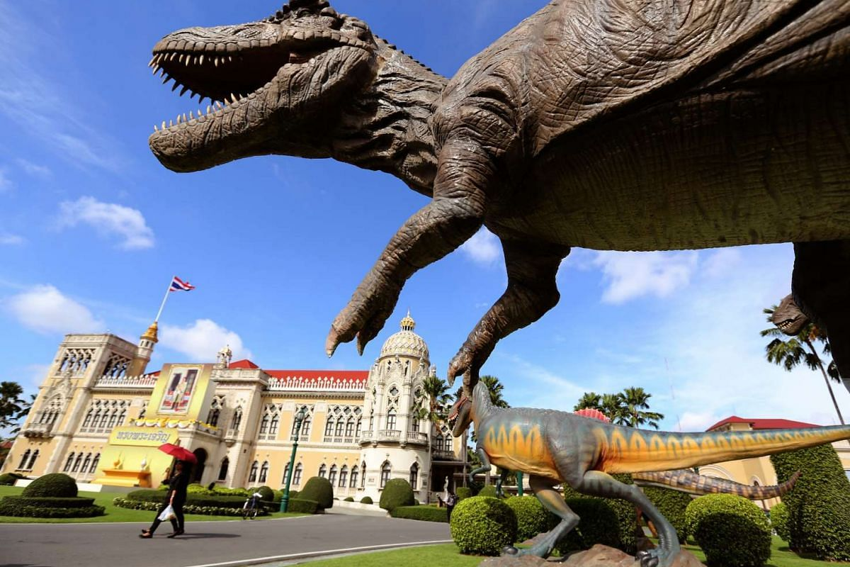 Thai government officials walk past the scale model of a dinosaur which was set up as a decoration in preparation for National Children's Day event at the compound of the Government House in Bangkok, Thailand,  January 12, 2017. PHOTO: EPA