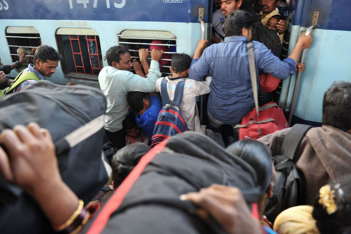 Indian passengers board a train at the Secunderabad Railway station in Hyderabad on January 12, 2017.  PHOTO: AFP