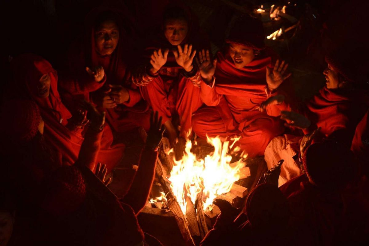 Nepalese Hindu women warm themselves beside fires after taking a bath in the holy Shali River on the outskirts of Kathmandu on January 12, 2017. PHOTO: AFP