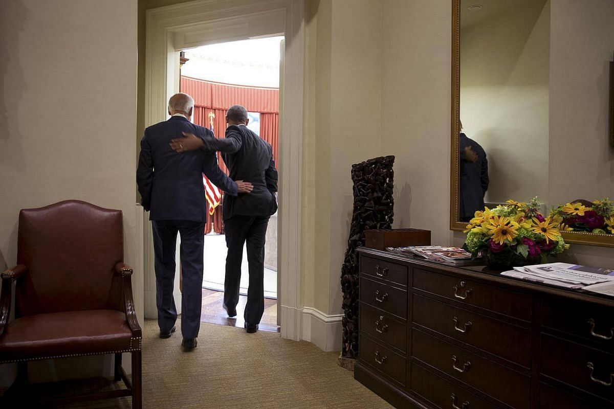 President Barack Obama and Vice-President Joe Biden embrace while walking into the Oval Office, at the White House, in Washington, on June 25, 2015.