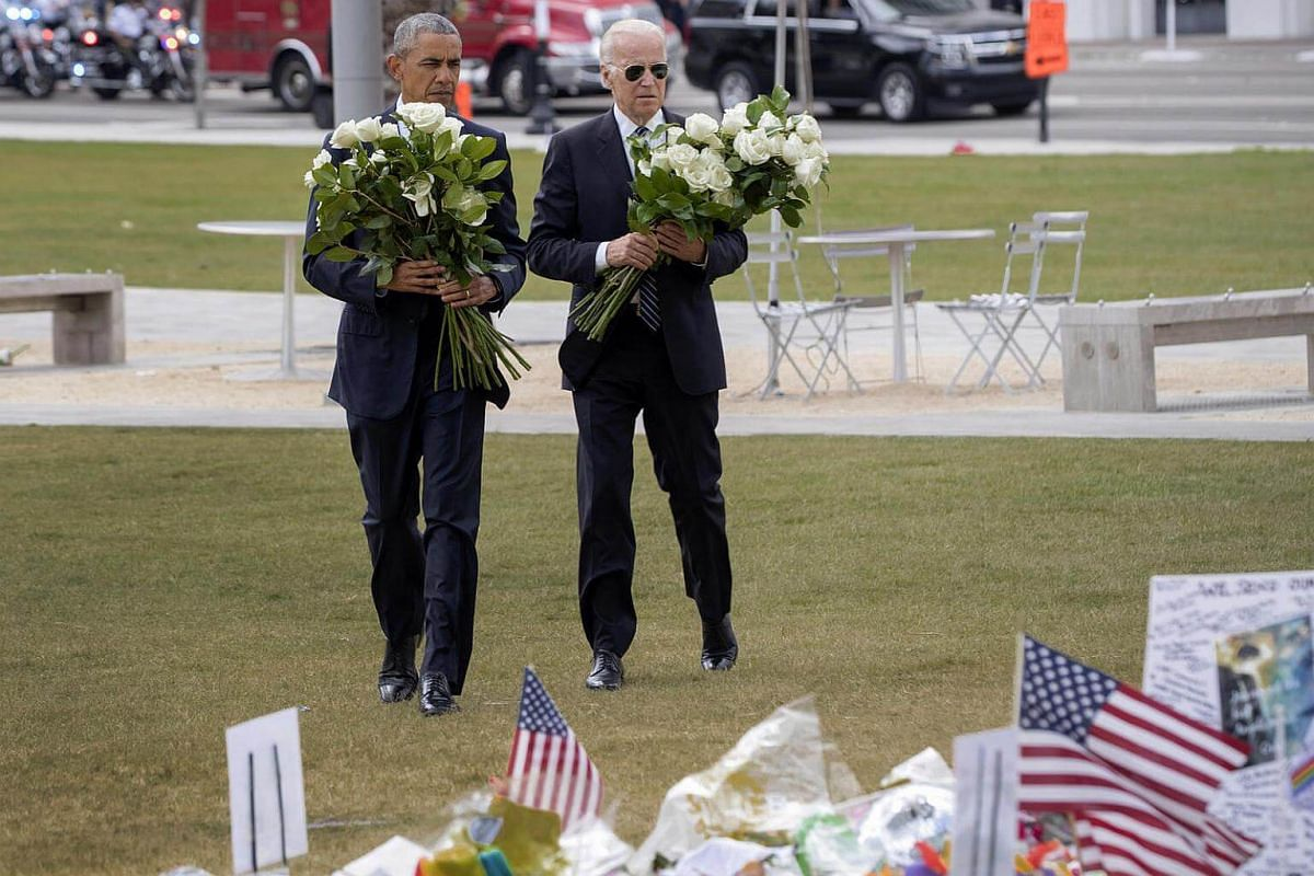 President Barack Obama and  Vice-President  Joe Biden carrying flowers during a visit to the makeshift memorial for the victims killed in the shooting at Pulse nightclub, outside Dr. Phillips Center for the Performing Arts in Orlando, Fla., on June