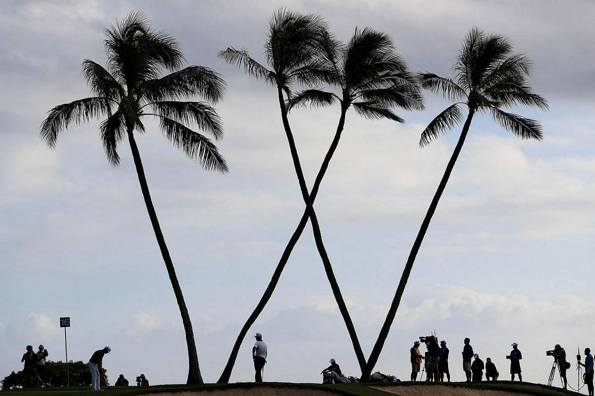 Zach Johnson of the United States putts as Justin Thomas of the United States and Justin Rose of England look on during the final round of the Sony Open In Hawaii at Waialae Country Club, on Jan 15, 2017.